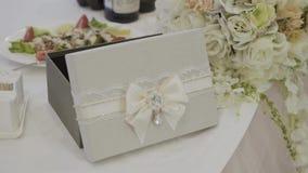 Invitaciones de la boda y pecho del dinero adornado con el cordón almacen de metraje de vídeo