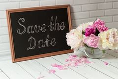 Invitation with bouquet of peonies and chalkboard Stock Photos