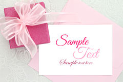 Invitation card. Gift box with ribbon and white invitation card royalty free stock image