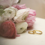 Invitation card. Ranunculus with wedding rings on vintage table Royalty Free Stock Photos