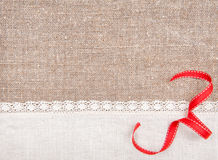 Invitation card with ribbon and linen fabric on the burlap Stock Image