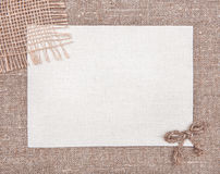 Invitation card with textile bow and sacking. On burlap background royalty free stock photos