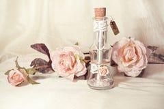 Invitation de mariage dans une bouteille en verre et des roses roses Photographie stock libre de droits
