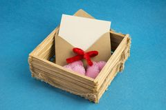 Invitation envelope in wooden wicker basket decorated with pink hearts on blue background. royalty free stock image