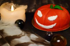 Invitation for Halloween pumpkin alchemist. The idea for baking and decorating for Halloween. An ominous orange pumpkin with white eyes and a mouth. He smiles stock images