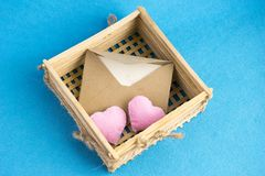 Invitation or love letter in old wooden wicker with plush hearts on blue background. Brown envelope with invitation for Valentines day celebration or wedding Stock Image