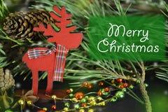 invitation new year Деревянная игрушка оленей с шарфом и рождеством надписи веселым стоковое изображение