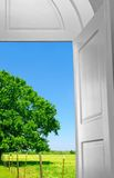 Invitation Outdoors. Open door leading to brightly colored meadow under blue sky Stock Photos