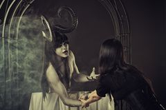 Invitation to Hell. Horrible pale demon pulling innocent gothic girl stock photography