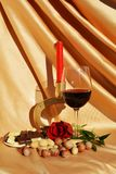 Invitation to romantic event. Wine, rose and chocolate, on an elegant golden background, as romantic invitation to love moments Royalty Free Stock Photos