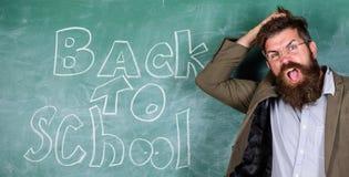 Invite a la escuela El profesor o el educador acoge con satisfacci?n a estudiantes mientras que los soportes cerca de la pizarra  fotografía de archivo libre de regalías