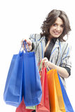 Invite to shopping. Happy young woman giving out colorful bags as an invitation to shopping Royalty Free Stock Image