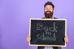 Invitera för att fira dag av kunskap Läraren uppsökte mannen står och rymmer svart tavla med inskriften tillbaka till skolan royaltyfri fotografi