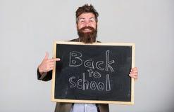 Invitera för att fira dag av kunskap Läraren uppsökte mannen står och rymmer svart tavla med inskriften tillbaka till skolan royaltyfri bild