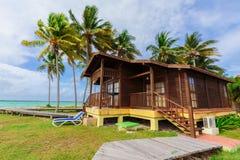 Invitera som är ursnyggt och att bedöva sikt av hotelljordning med bungalowslags tvåsittssoffa, bekväma hus som står på stranden  arkivbilder