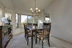 Inviterande ljus fyllde matsal med den wood äta middag tabellen Royaltyfri Foto