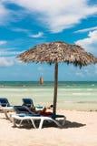 Inviterande vardagsrumstolar under det tropiska paraplyet på stranden, sai arkivbild