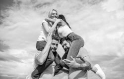 Inviting another couple to join. Friendship of families. Twice fun on double date. Couples in love having fun. Men carry. Girlfriends on shoulders. Summer stock photo