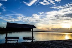 Inviting beaches on a peaceful lake. In the Carolina`s. Sunset is staring with rays coming out from the clouds. Blues and yellows Royalty Free Stock Images