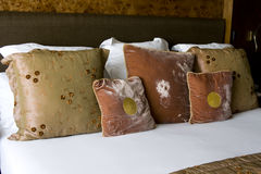 Inviting bed with many big soft cushions. Inviting, warm bedroom suite with warm earthy colored cushions to rest against Royalty Free Stock Photography