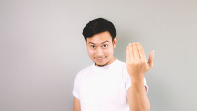 Inviting or calling hand sign. An asian man with white t-shirt and grey background Stock Photos