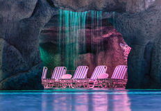 Inviting  Cozy comfortable grotto in swimming pool at night time. Night view of swimming pool with cozy warm grotto and beach lounges inside Stock Image