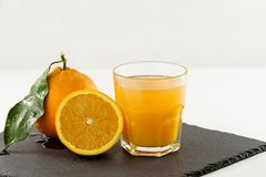 An inviting glass full of orange juice, a half orange and a whole one with leaf on a square slate plate on white background. An inviting glass full of orange stock photography