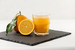 An inviting glass full of orange juice, a half orange and a whole one with leaf on a square slate plate on white background stock photo