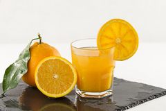 An inviting glass full of orange juice with orange slice on the rim, a half orange and a whole one with leaf on a square wet slate. Plate on white background stock photography