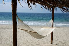 Inviting hammock on the beach. A hammock overlooking a sandy beach and a deep blue ocean Stock Photo