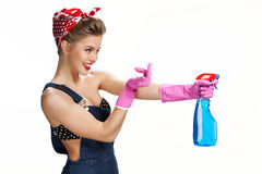 Inviting housewife wearing pink rubber protective gloves holding spray Royalty Free Stock Images
