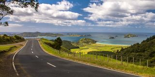 Inviting road through New Zealand countryside with blue sea Stock Photos