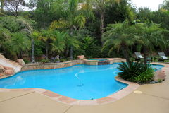 Inviting Scene Of Backyard Oasis With Pool, Chairs And Beautiful Landscape Stock Photo