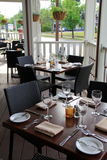 Inviting scene of tables set for dinner,Thirsty Owl,Saratoga Springs,New York,2015. Inviting scene of tables set for dinner on outside porch,Thirsty Owl Stock Photography