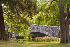 Inviting seat in shade by stone bridge Royalty Free Stock Image