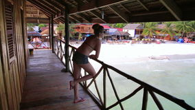 Inviting tourist girl at bungalow with beach view stock video footage