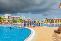 Inviting view of comfortable cozy swimming pool with entertainment team and swimmers in background. Cayo Guillermo island, Iberostar Playa Pilar hotel, Cuba Royalty Free Stock Images