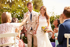 Invités jetant des confettis au-dessus des jeunes mariés At Wedding Photographie stock libre de droits