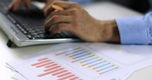 Invoer van gegevens - bediende die met statistische grafieken werken en op toetsenbord typen stock video