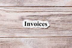 Invoices of the word on paper. concept. Words of Invoices on a wooden background.  Stock Photo