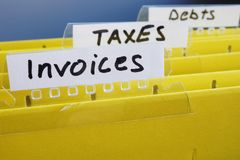 Invoices written on folder with documents. Invoices written on a yellow folder with documents Stock Images