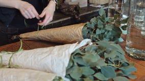 Involucri del fiorista della donna qualcosa in uno strato di pergamena e del nastro di bendaggio stock footage