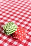Involucri del muffin del Libro Verde rosso e sulla tavola Fotografie Stock
