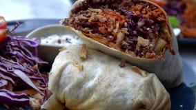 Involucro della tortiglia del vegano, rotolo del burrito con i vegetabes arrostiti Stili di vita di salute e della sostenibilità stock footage