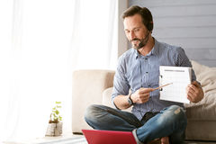 Involved bearded man using modern gadgets at home Stock Image
