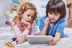 Involved boy and girl watching tablet in children room stock photo