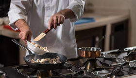 Involved chef frying mushrooms in the kitchen of the restaurant Royalty Free Stock Image