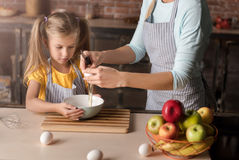 Involved daughter breaking eggs with her mother in the kitchen Royalty Free Stock Photography