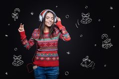 Involved delighted girl enjoying Christmas songs. Enjoyable Christmas melodies. Cheerful delighted inspired girl standing against imaginary drawing on the black Stock Image