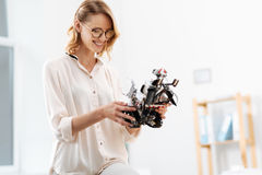 Involved engineer exploring futuristic robot functions in the laboratory. Time for tech check up. Clever cute concentrated technology specialist enjoying working Stock Image